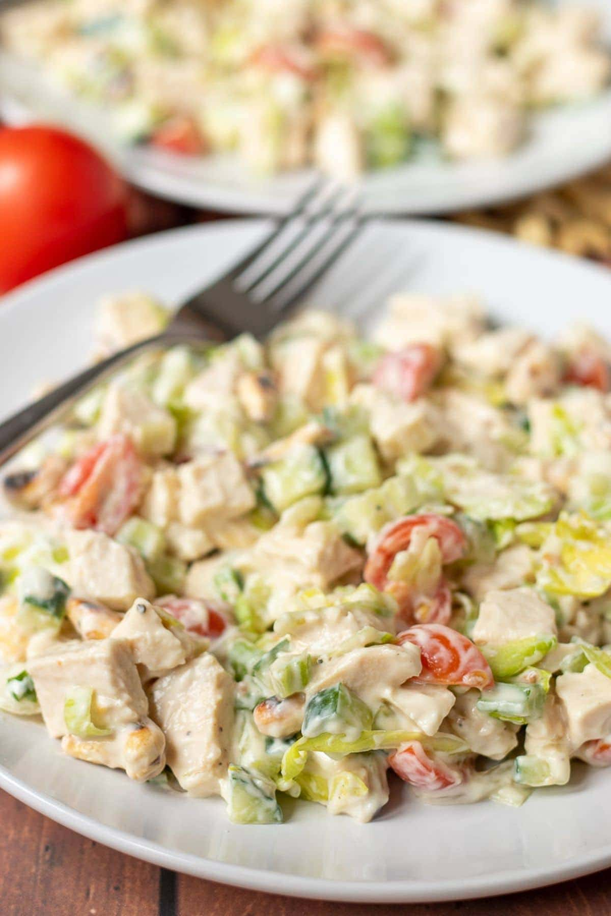 Close up of a plate of quick healthy chicken salad with a fork on.
