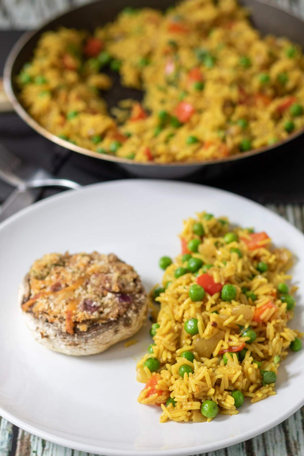 Close up of spicy rice with peas served alongside a stuffed garlic mushroom. Remainer of the rice in a pan in the background.