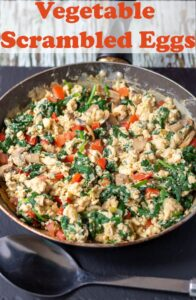 A pan of cooked vegetable scrambled eggs with a spoon in front. Pin title text overlay at top.
