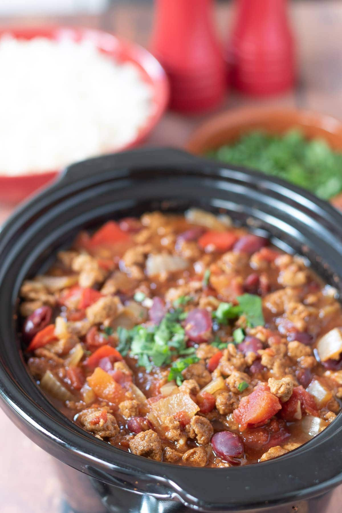 Birds eye view of slow cooker vegetarian chilli in slow cooker garnished with freshly chopped coriander.