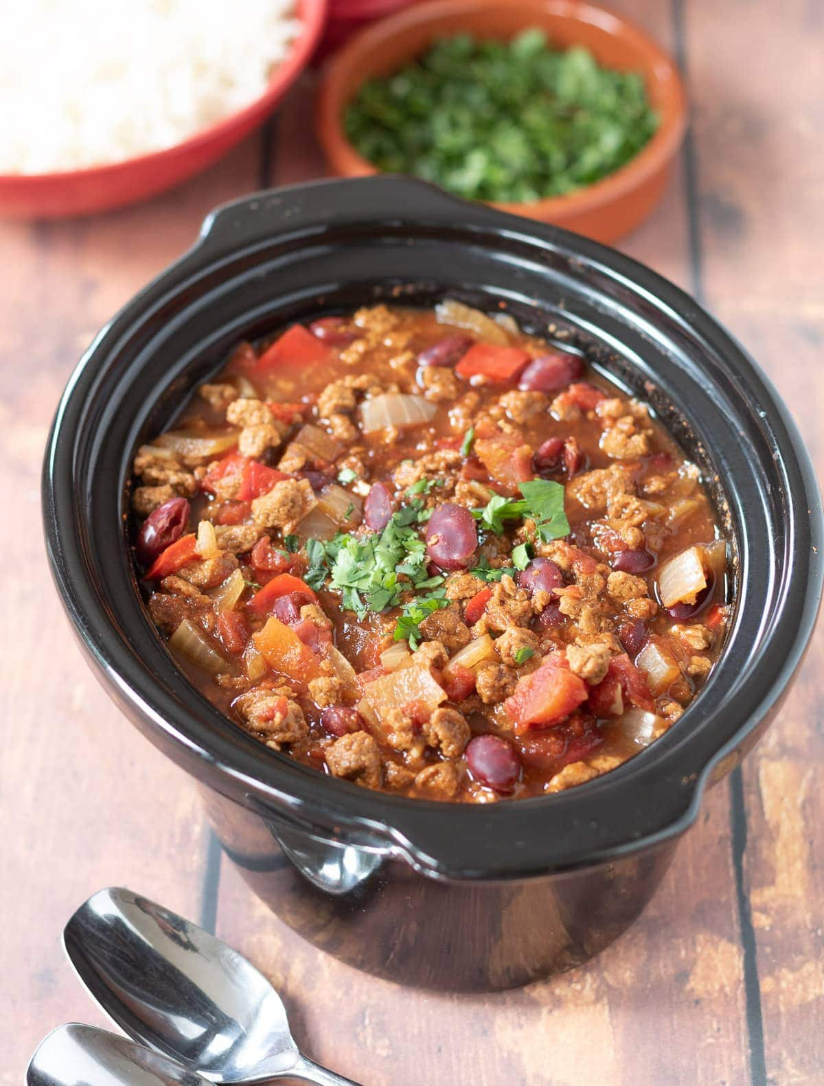 Slow cooker vegetarian chilli in slow cooker. Dishes of rice and coriander at the top.