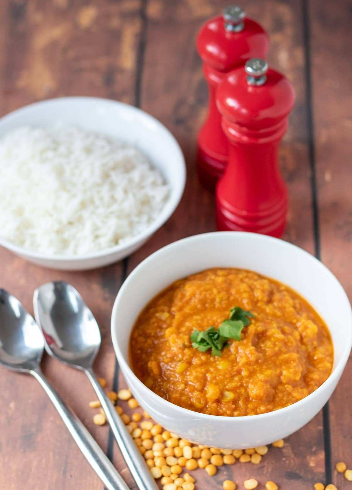 A bowl of yellow lentil dahl garnished with coriander at the front. Serving spoons to the left, a bowl of rice and salt and pepper cellars in the background.