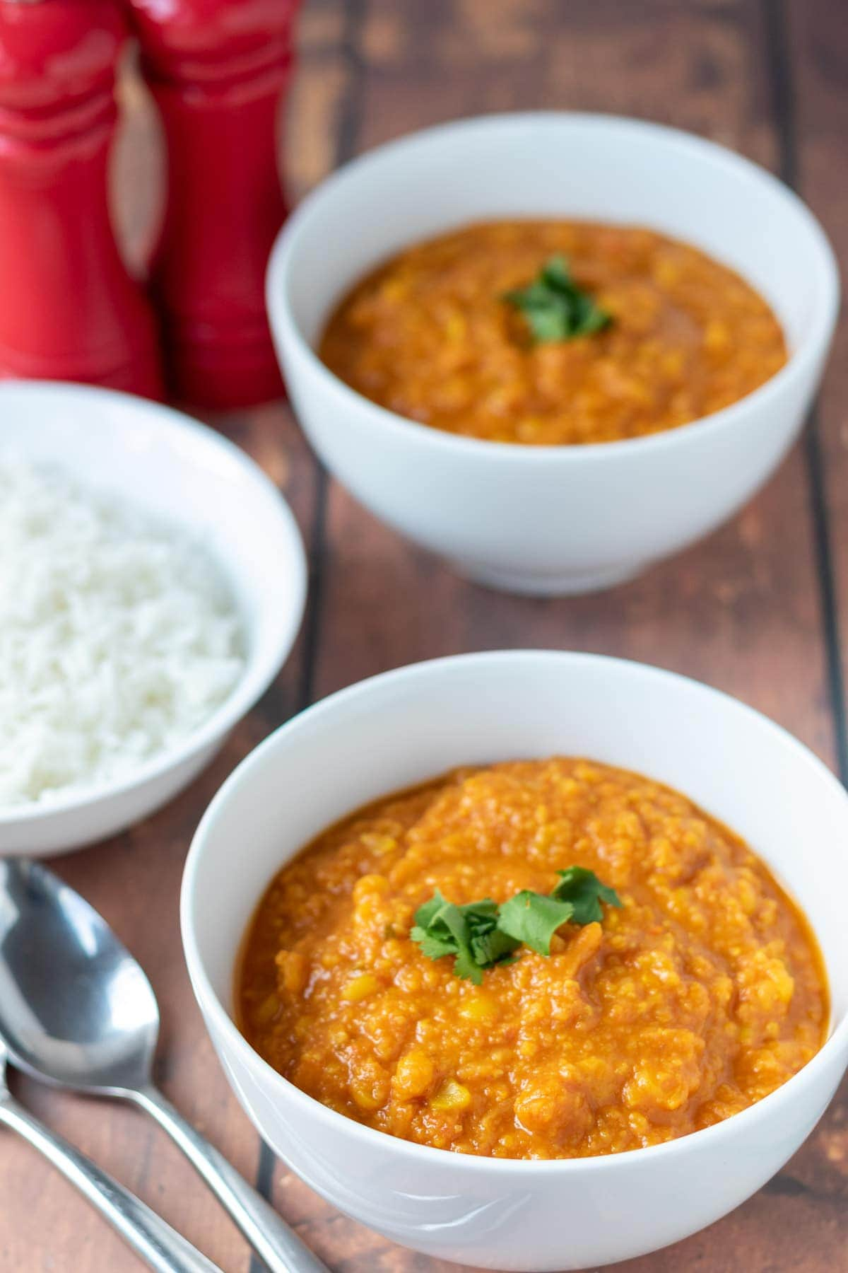 Two bowls of yellow lentil dahl one in front of the other garnished with coriander. A bowl of rice and spoons to the left hand side.