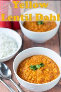Two bowls of yellow lentil dahl with a bowl of rice to the side and spoons to eat with. Pin title text overlay at top.