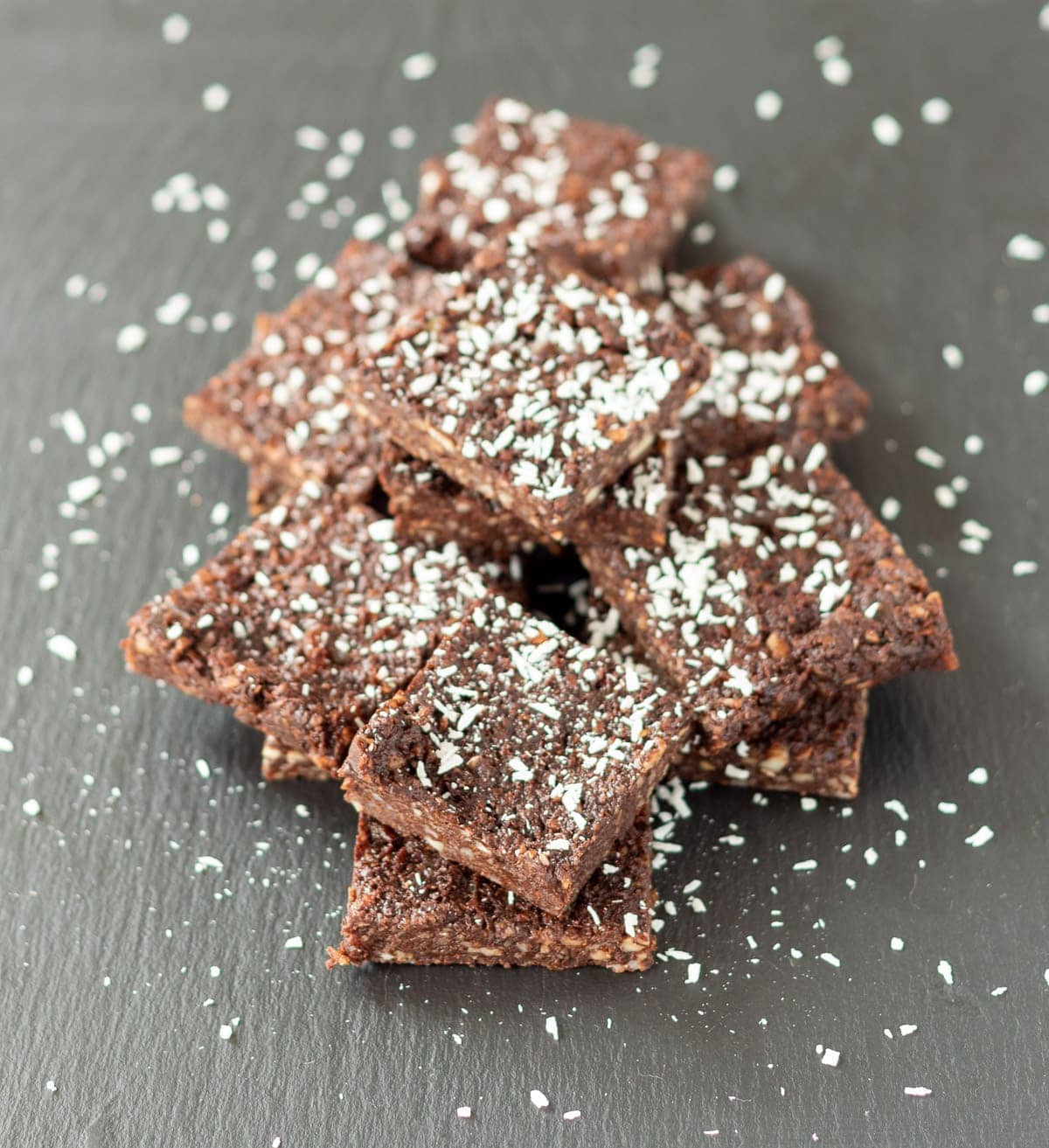 Birds eye view of a stack of 5-Ingredient no bake chocolate brownies on a slate decorated with grated coconut.