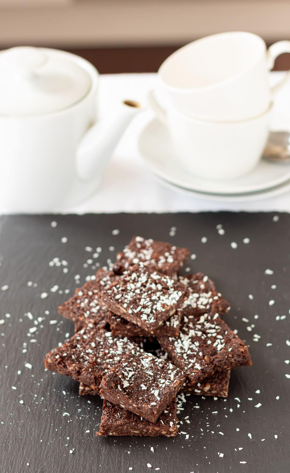 No bake chocolate brownies on a black slate decorated with grated coconut. A tea pot and two tea cups on a saucer at top of picture.