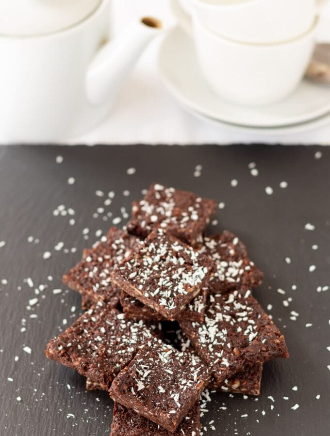 A stack of 5-ingredient no bake chocolate brownies on a slate decorated with grated coconut. A tea pot and tea cup at top of picture.