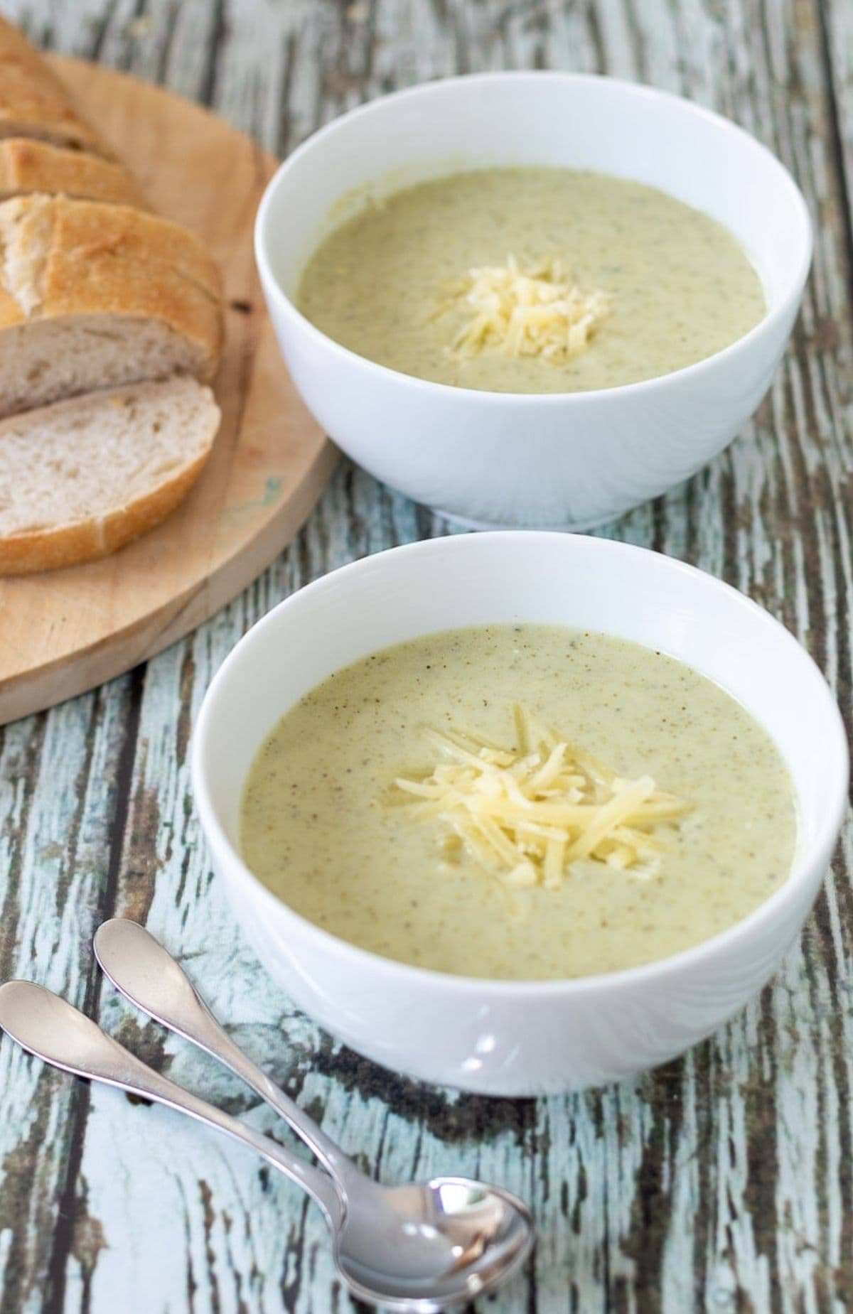Two bowls of broccoli and potato soup garnished with some grated cheese. Sliced bread on a board to the side.