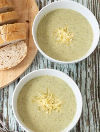 Birds eye view of two bowls of broccoli and potato soup garnished with some grated cheese. Sliced bread on a board to the side.
