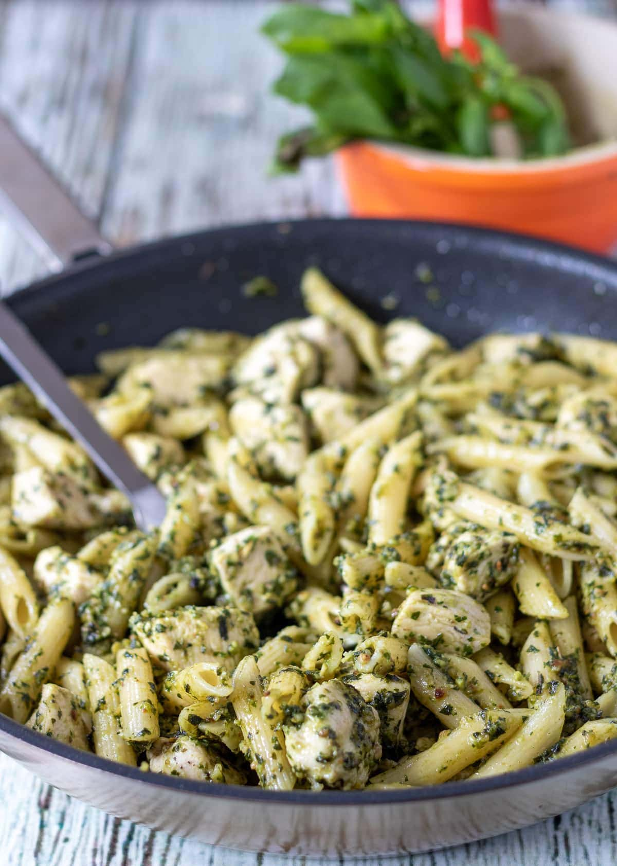 Close up of a pan of cooked chicken pesto pasta with a serving spoon in ready to serve. Pestle and mortar in the background.