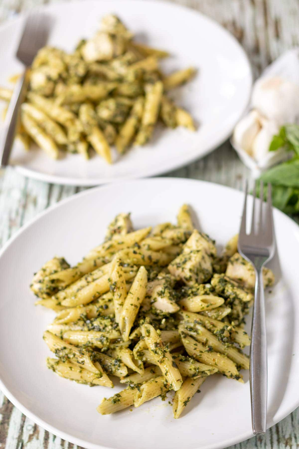 Two plates of chicken pesto pasta with forks on ready to eat.
