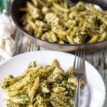 A plate of cooked chicken pesto pasta with a fork to the right hand side. A frying pan of the rest of the cooked dinner in the background.