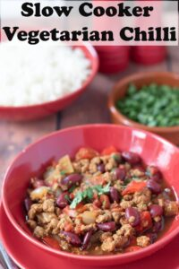 A bowl of slow cooker vegetarian chilli garnished with chopped coriander. A dish of chopped coriander and bowl of basmati rice in the background. Pin title text overlay at top.