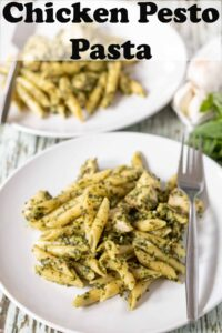 Two plates of chicken pesto pasta one in front of the other with forks on. Pin title text overlay at top.