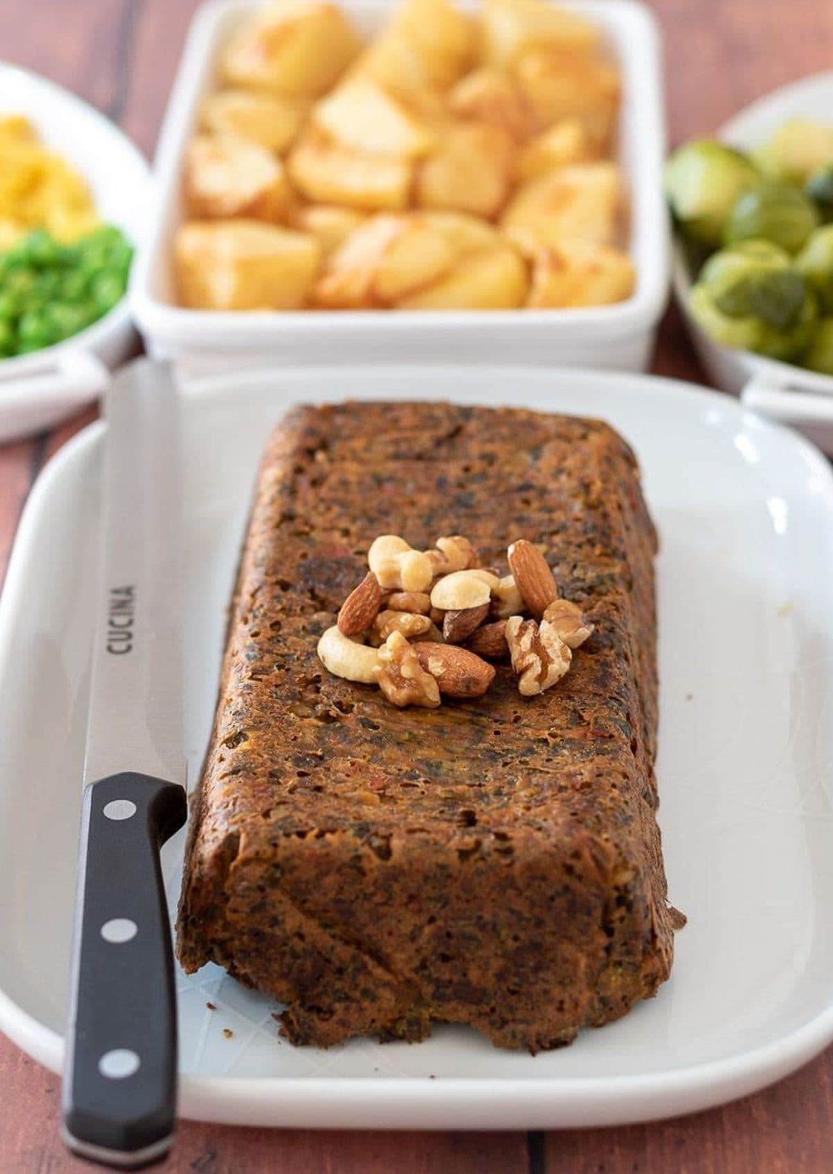 Festive nut roast served on a square serving plate with a knife to the side. Side dishes of roast potatoes, peas, sweetcorn and sprouts in the background.