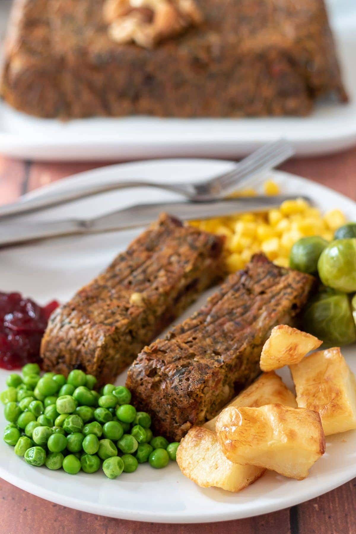 Festive nut roast served with roast potatoes, peas, sprouts, sweetcorn and cranberry sauce.