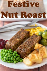 A plate with two festive nut roast slices on including peas, roast potatoes, sweetcorn and brussel sprouts. Cranberry sauce and a fork to the side. Pin title text overlay at top.