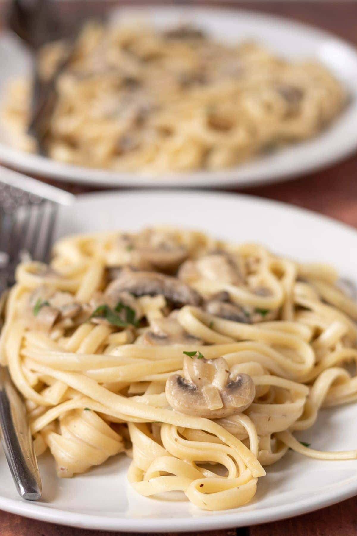 Close up of a plate of low fat garlic mushroom pasta with forks on. Another plate in the background.