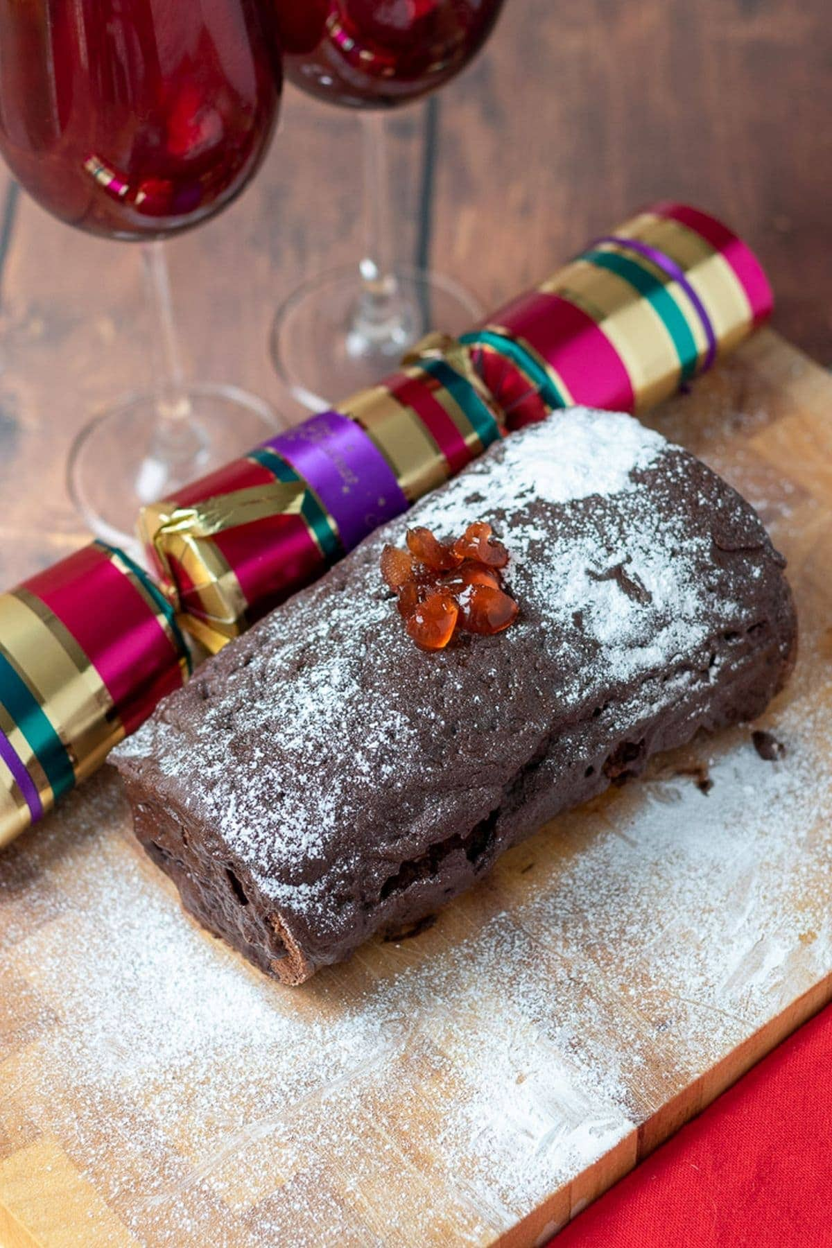 Traditional chocolate log on a chopping board decorated in chocolate ganache, icing sugar and chopped cherries. A christmas cracker alongside the board.