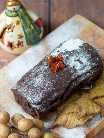 The best chocolate log on a chopping board covered in chocolate ganache, icing sugar and chopped cherries. Assortment of Christmas decoration around.