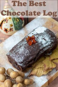 Home made chocolate log on a board topped with red berries and icing sugar. Christmas decorations around.