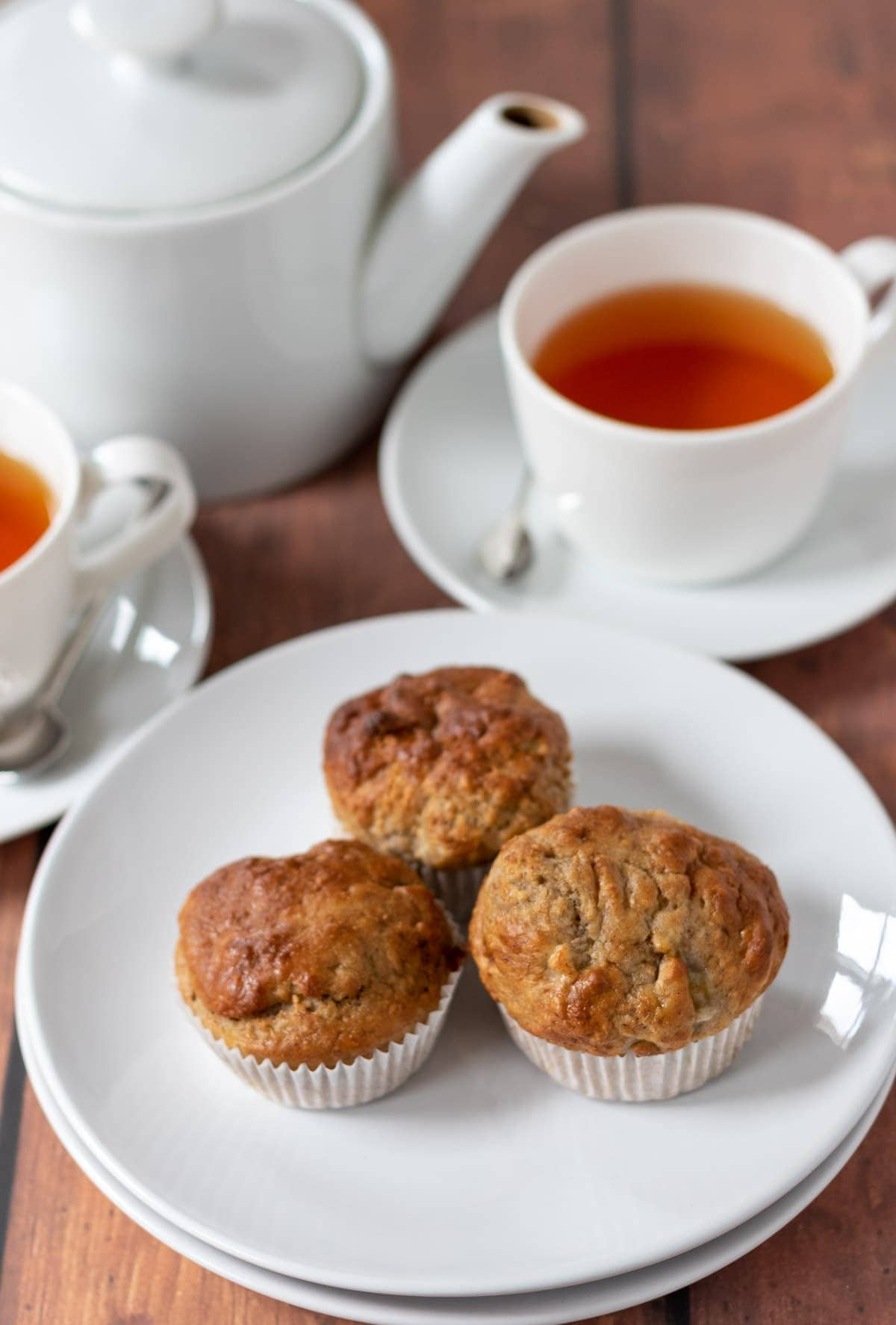 Three banana bread muffins on a plate with two cups of tea and a tea pot in the background.