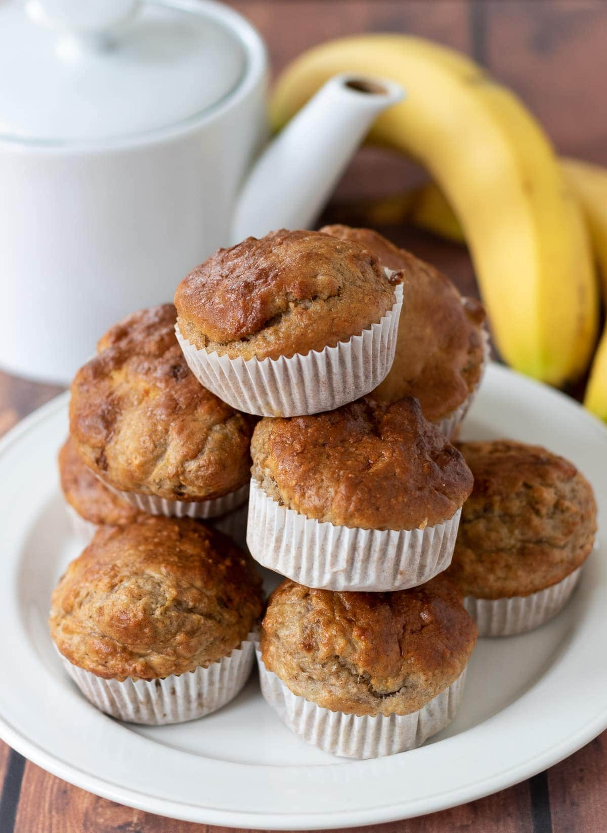 Banana bread muffins stacked on a plate with a tea pot and two bananas in the background.