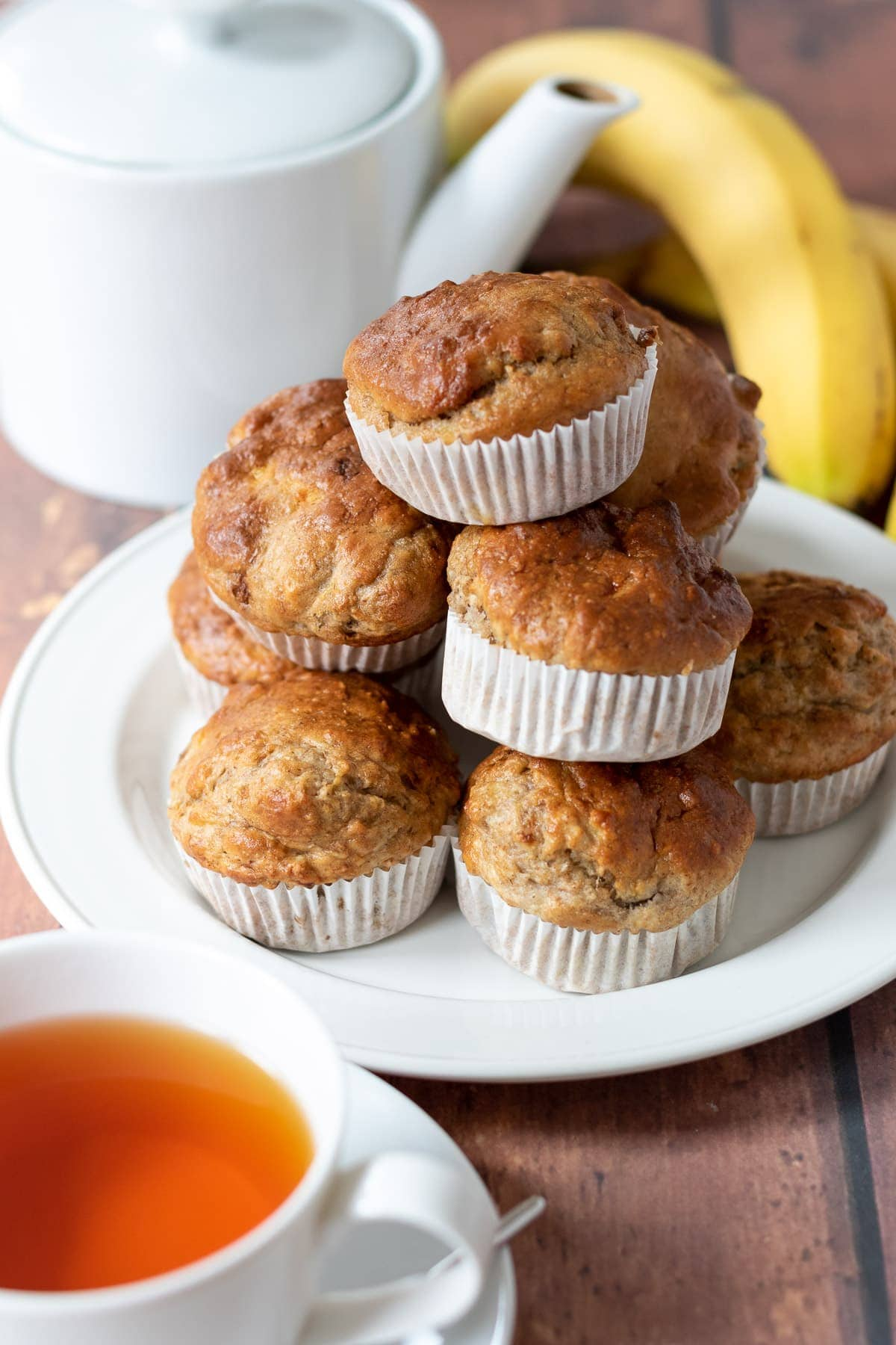 A stack of banana bread muffins on a plate. Cup of tea in the foreground and a teapot and banana in the background.
