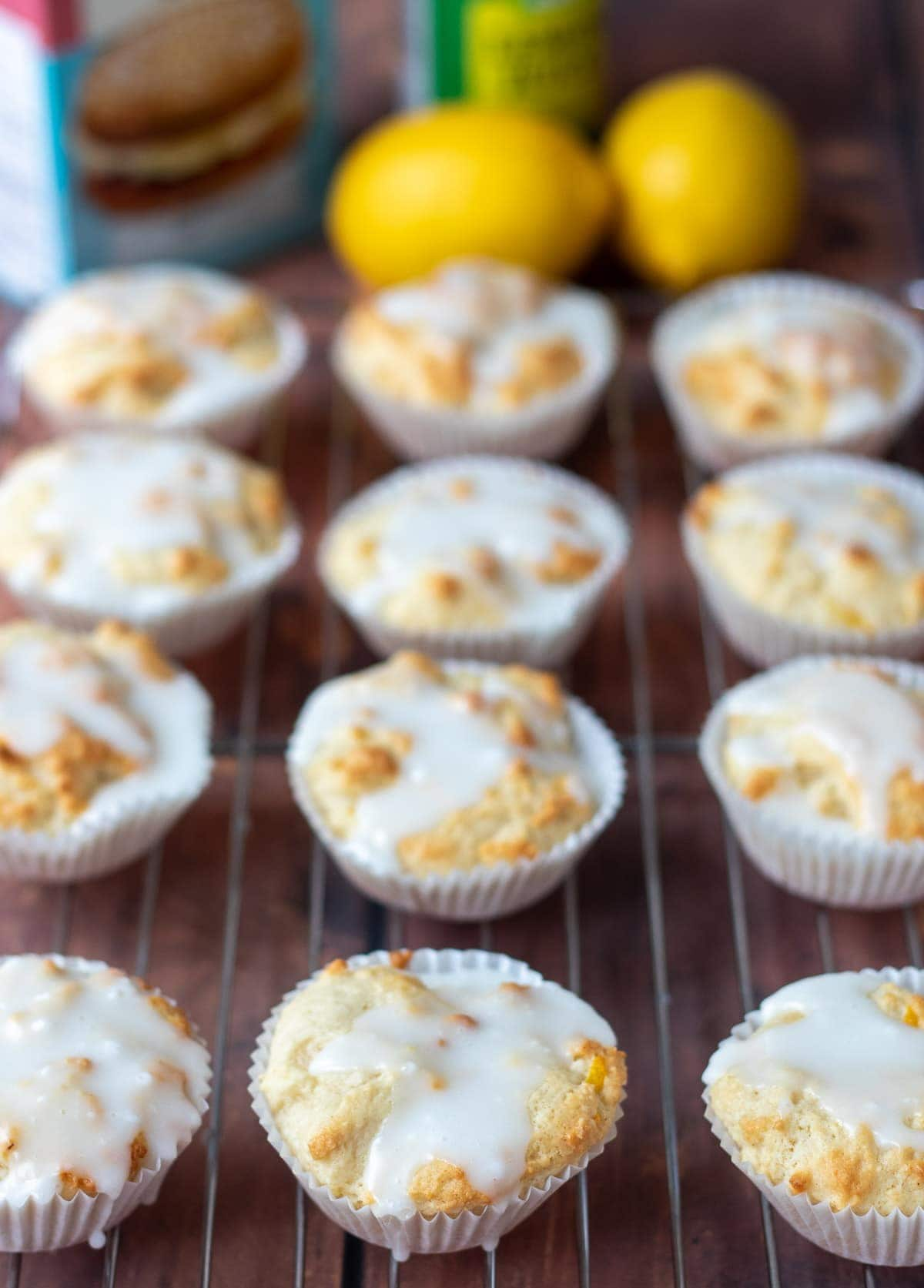A wire rack of twelve iced easy lemon cupcakes. Two lemons and other ingredients boxes in the background.