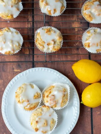 Birds eye view of a plate of three easy lemon cupcakes topped with icing. Two lemons to the right side and three cupcakes on a wire rack at the top.