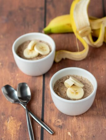 Two ramekins of healthy banana pudding topped with sliced bananas. Two bananas in the background and two teaspoons in the foreground.