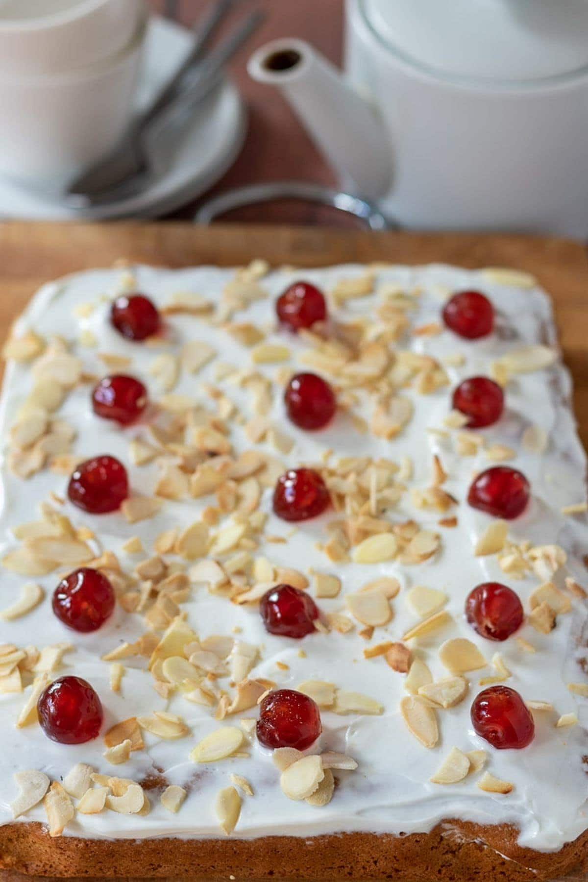 Cherry Bakewell removed from baking tin, decorated with glace cherries and sitting on a chopping board ready to be cut into squares. A pot of tea and tea cup in the background.