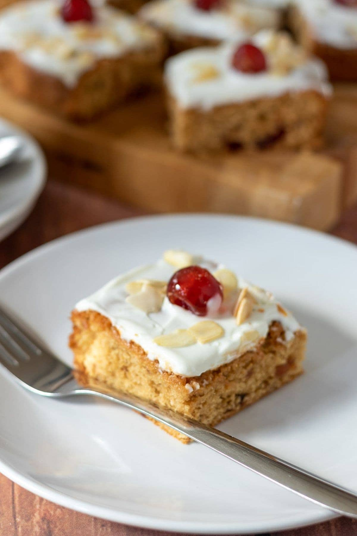 A slice of cherry Bakewell tray bake served on a white plate with a fork to the side. Chopping board with the rest of the tray bake squares on in the background.