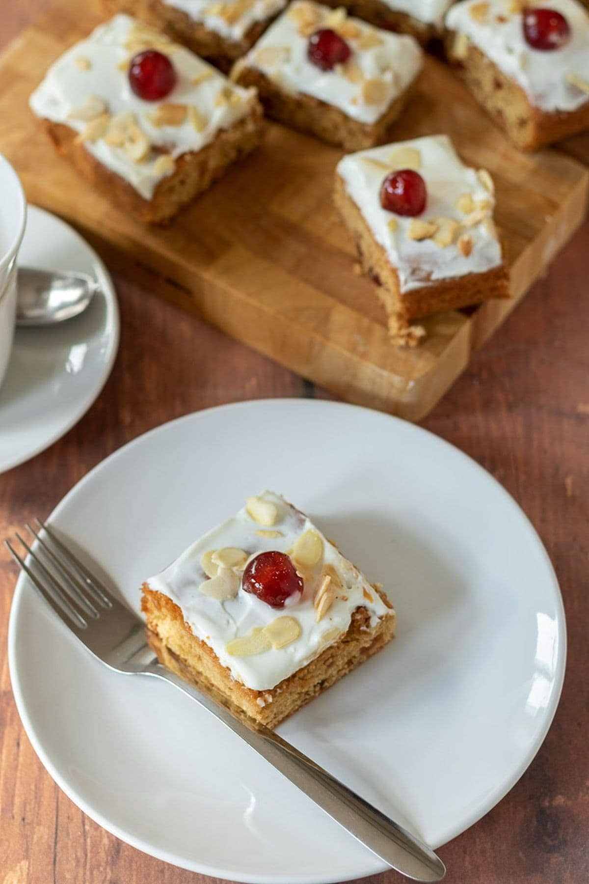Birds eye view of a slice of cherry Bakewell tray bake served on a white plate with a fork to the side. Chopping board with the rest of the tray bake squares on in the background.
