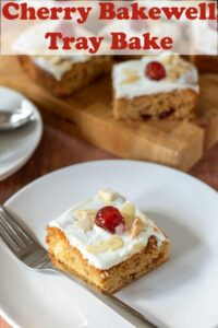 A slice of cherry bakewell tray bake topped with cream cheese icing and a glace cherry on a plate. Rest of the slices on a board in the background. Pin title text overlay at top.