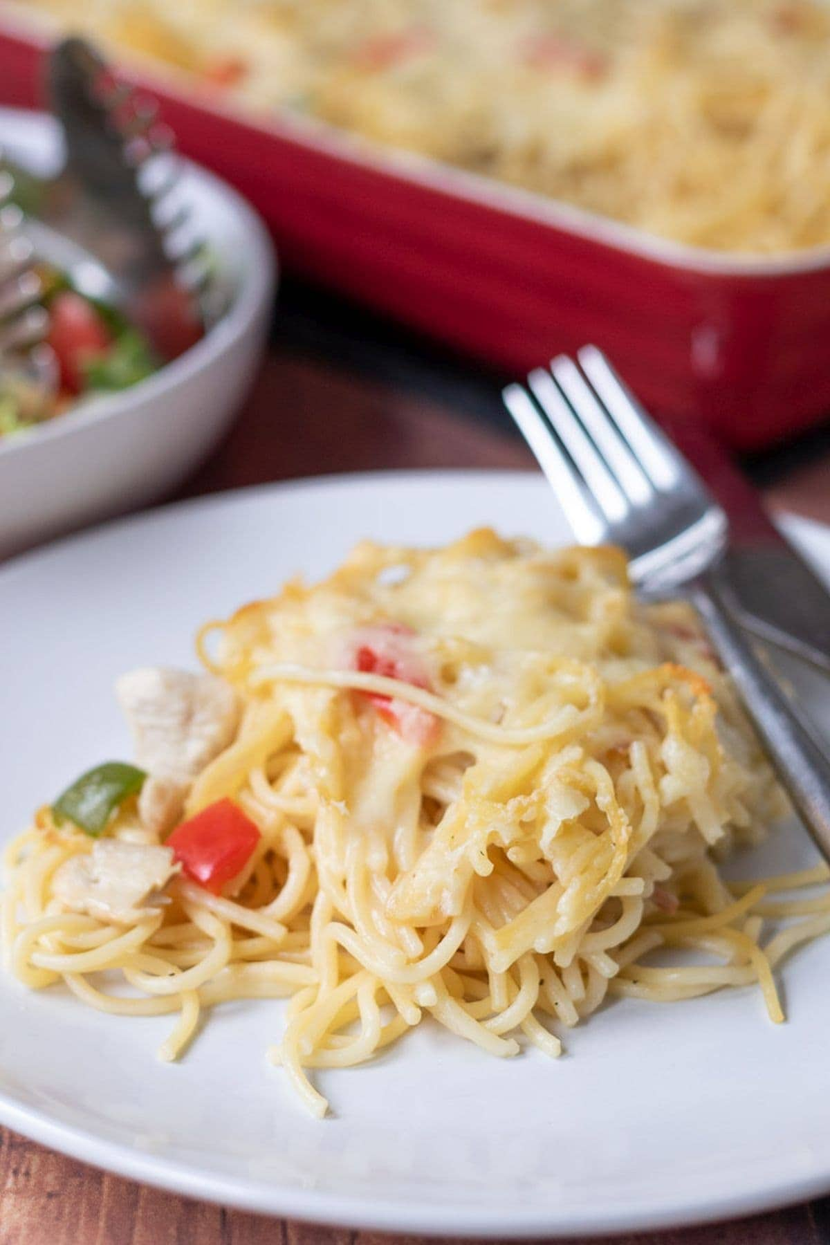 A plate with a portion of chicken spaghetti bake served on. Rest of the bake in a casserole dish in the background. A bowl of salad in between.