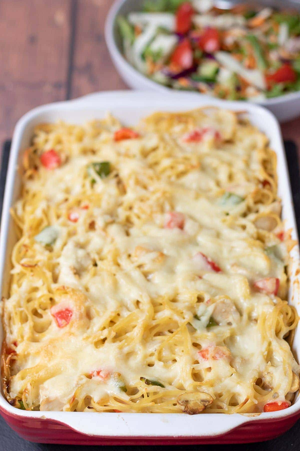Chicken spaghetti bake in a large red stoneware dish. A bowl of salad in the background.