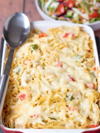 Chicken spaghetti bake in a large red stoneware dish with a serving spoon to the left. A bowl of salad in the background.