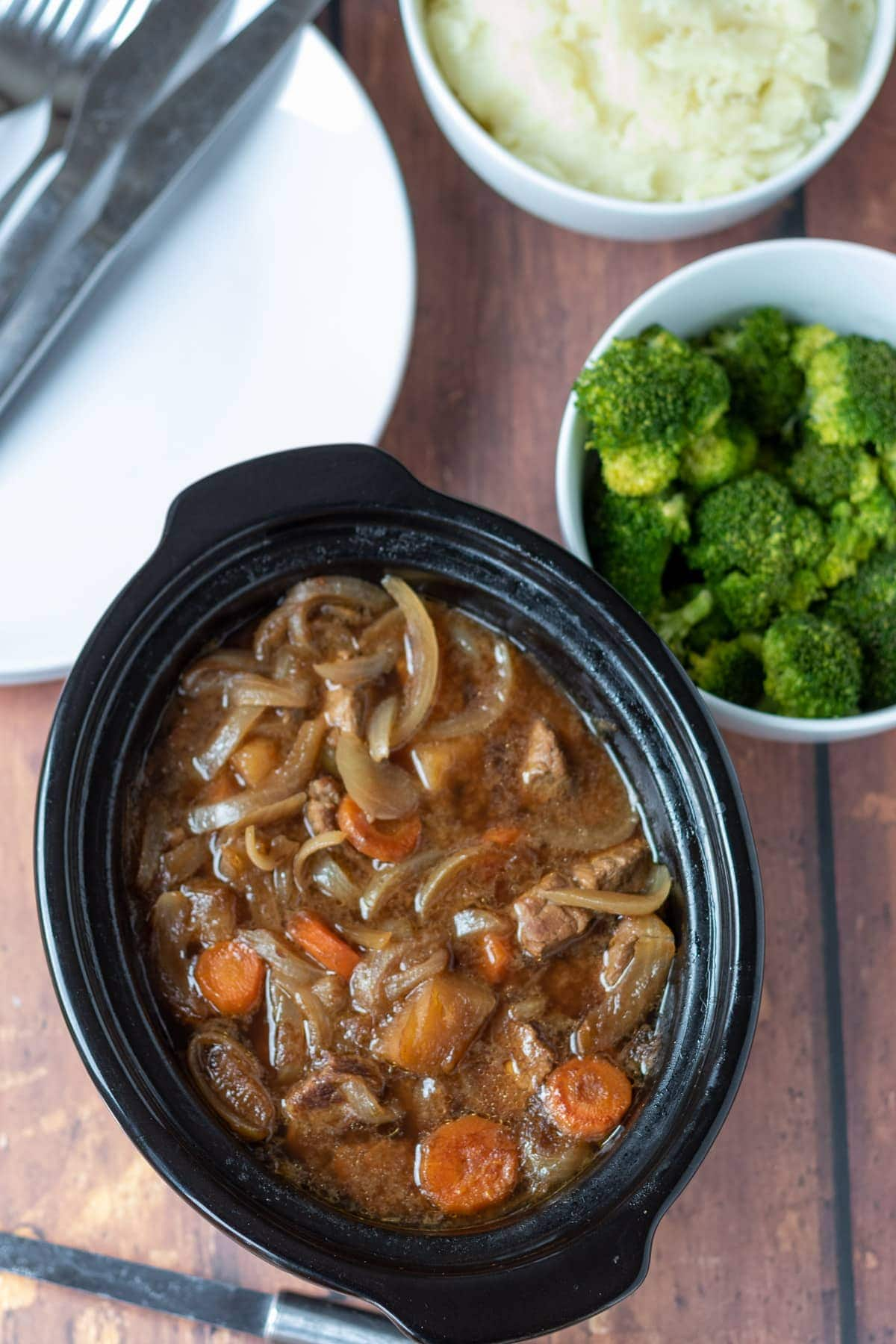 Birds eye view of slow cooker beef and ale stew. Side dishe of broccoli at the top right. Serving plates with cutlery on to the top left.