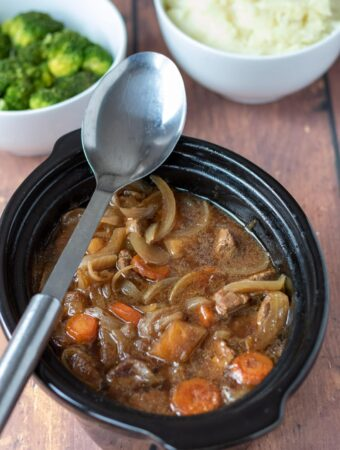Slow cooker beef and ale stew with a serving spoon placed over the top. Side dishes of broccoli and mashed potatoes at the top.