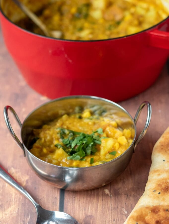 One pot vegetable dhal served in a balti dish with the rest in a casserole pot in the background. Spoon and Naan bread at the front.