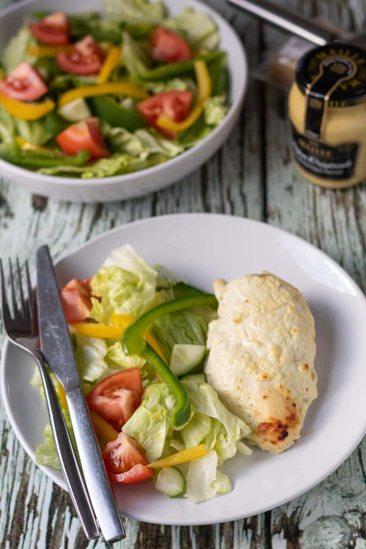 Oven baked mustard yogurt chicken served on a plate with salad and a knife and fork. Jar of mustard and bowl of salad in the background.