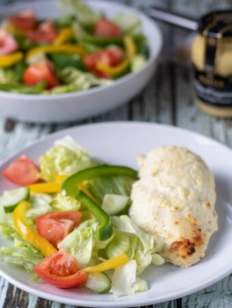 Oven baked mustard yogurt chicken served on a plate with salad. Jar of mustard and bowl of salad in the background.