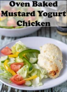 A plate with oven baked mustard yogurt chicken served with a salad. Pin title text overlay at top.