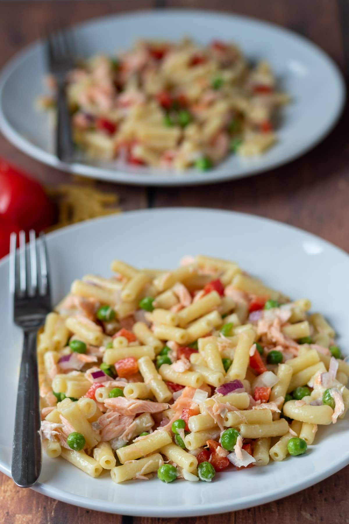 Two plates of salmon macaroni salad one in front of another with forks on.