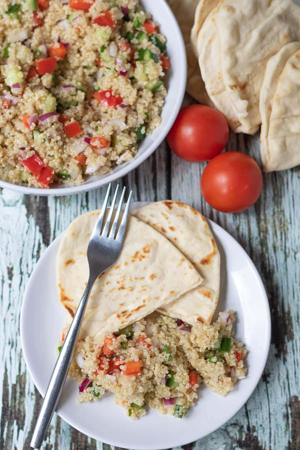 Birds eye view of a plate with a serving of quick quinoa salad on and two flatbreads with a fork on top. Rest of the quinoa salad in a bowl at the top with tow tomatoes and flatbreads beside.