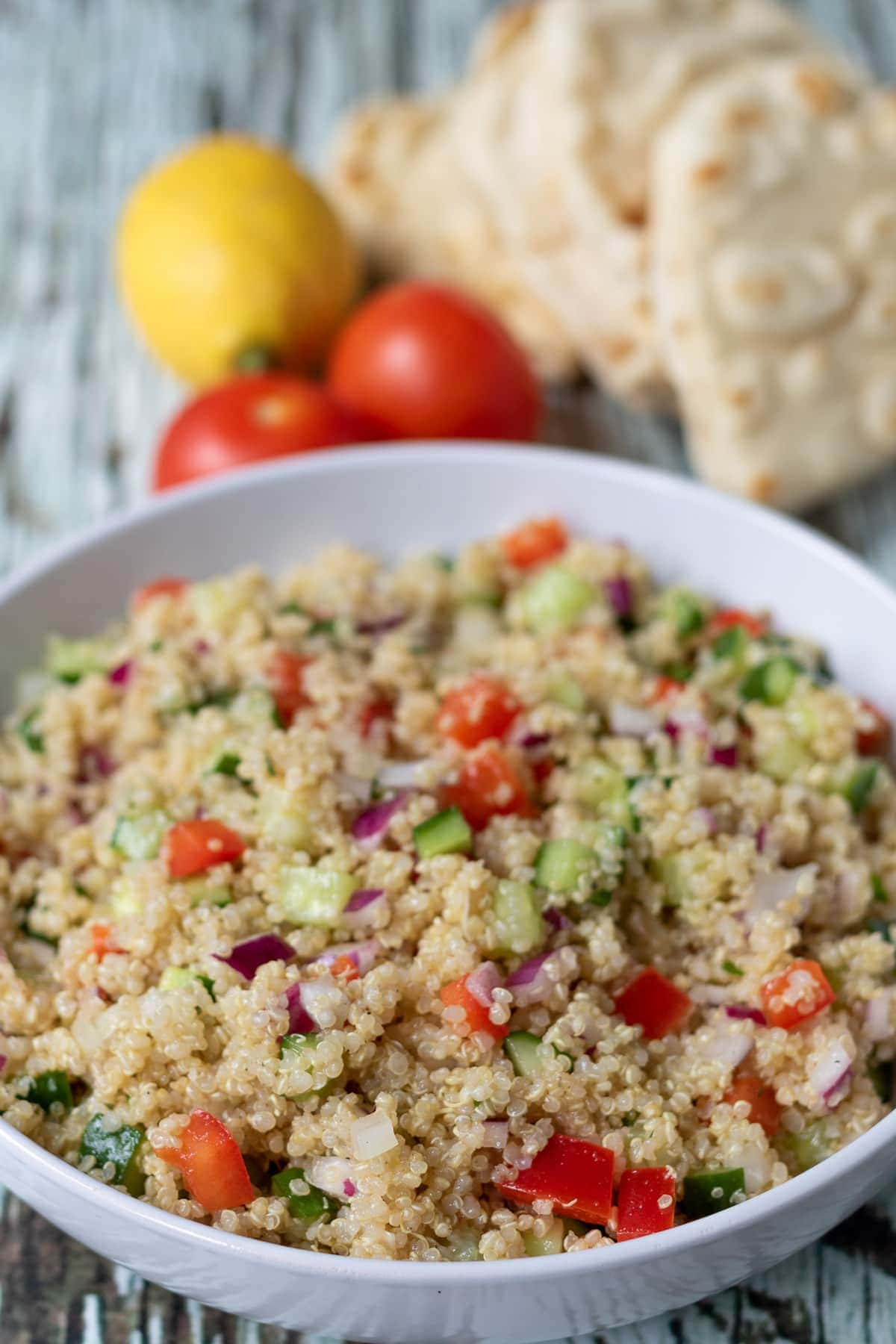 Close up of a bowl of quick quinoa salad with two tomatoes, a lemon and stack of flatbreads in the background.