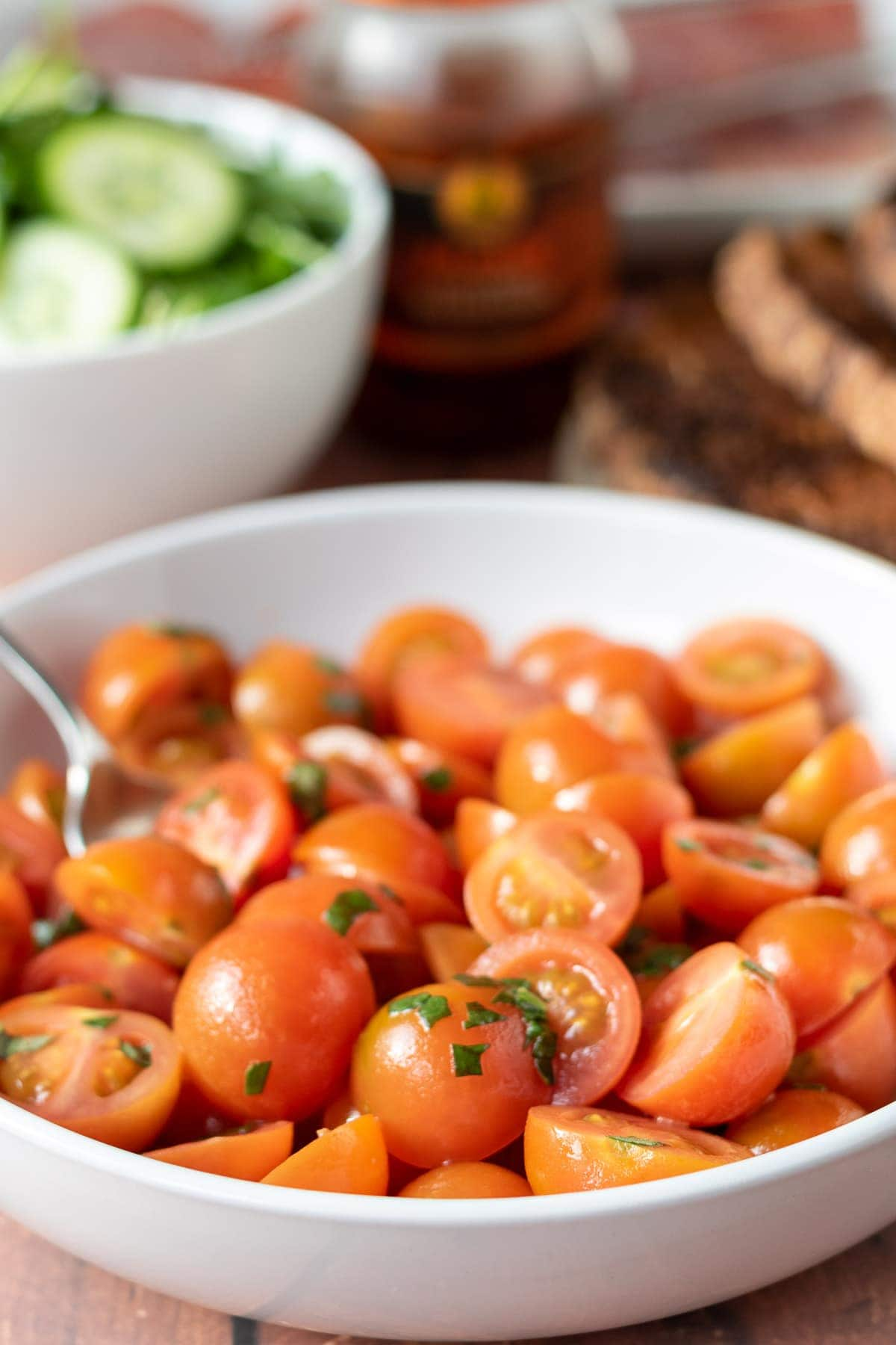 A bowl of tomato salad with another bowl with sliced cucumber in and a place of tasted bread in the background.