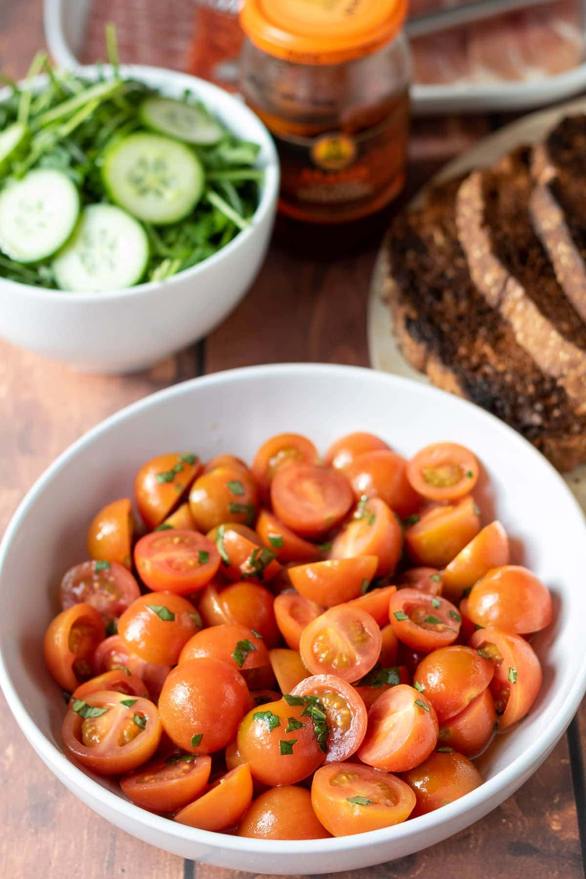 A bowl with cherry tomatoes in covered in a sweet dressing. In the background a bowl of sliced cucumber with a plate of tasted bread beside.