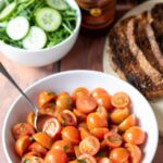 A bowl of cherry tomato salad with a bowl of cucumber, sliced bread and cold meat platter alongside.